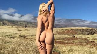 Gorgeous blonde Anikka Albrite posing among cloud-shrouded mountains